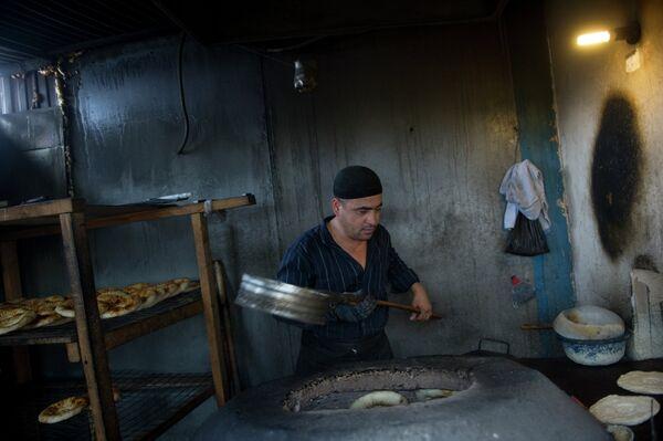 Иностранный рабочий печет лепешки в хостеле для мигрантов. Архивное фото - Sputnik Таджикистан