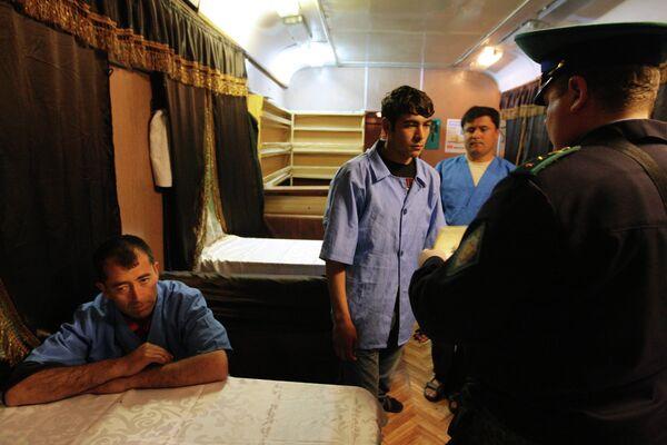Сотрудник погранслужбы проверяет документы у пассажиров поезда Душанбе-Москва. Архивное фото - Sputnik Таджикистан