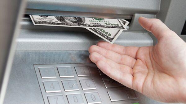 Банкомат выдает наличные деньги. Архивное фото - Sputnik Таджикистан