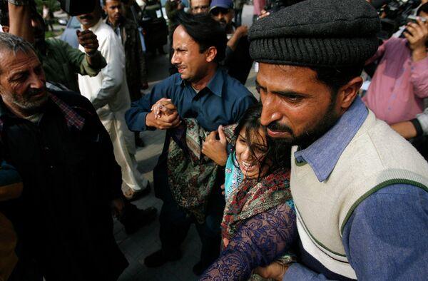 Мужчины утешают женщину, оплакивающую гибель своего родственника, который был убит в результате взрыва здания Главного полицейского управления в Лахоре, 17 февраля - Sputnik Таджикистан