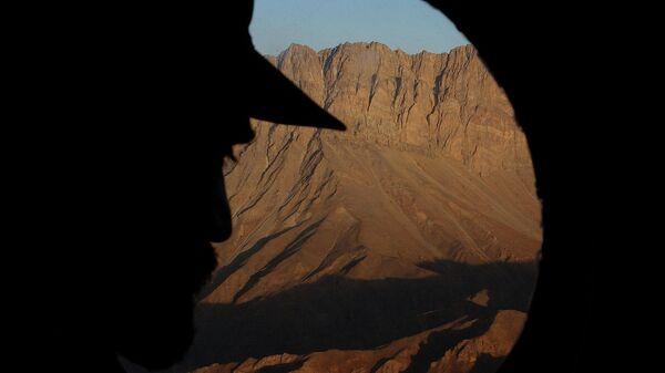 офицер смотрит в иллюминатор вертолета, пролетая над районом Дарваза, граничащим с Таджикистаном. Архивное фото - Sputnik Таджикистан