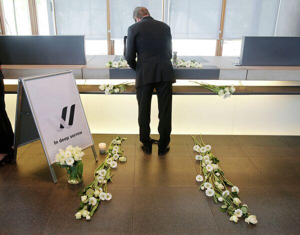 Сотрудник Lufthansa  делает запись в книге соболезнований жертвам самолета, потерпевшего крушение во французских Альпах. Франкфурт, 25 марта 2015 года - Sputnik Таджикистан