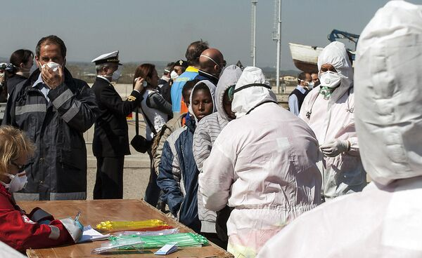 Выжившие мигранты в порту  Кориглано (Италия) после крушения судна  в 120 километрах от итальянского острова Лампедуза - Sputnik Таджикистан