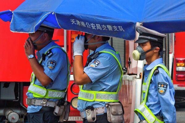 Сотрудники китайской дорожной полиции работают в респираторах на КПП около места взрыва. - Sputnik Таджикистан