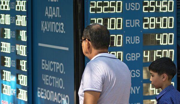 Мужчина с ребенком у информационного табло обменного пункта валюты в Алматы - Sputnik Таджикистан