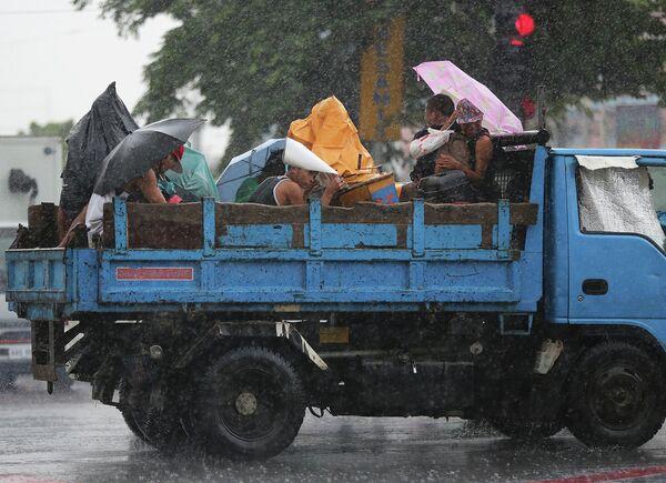 Люди укрываются от дождя во время сильного ливня в Маниле 24 августа 2015 года - Sputnik Таджикистан