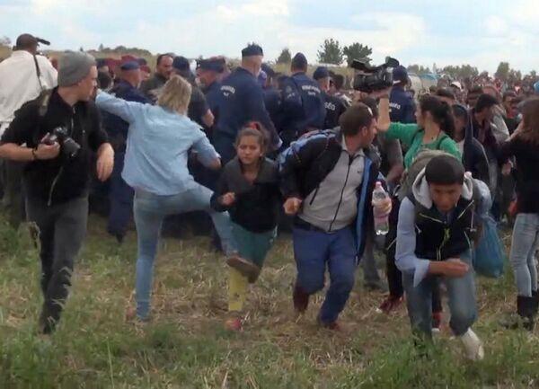 Скриншот с видео, на котором оператор телеканала Петра Лазло ставит подножку сирийским беженцам, убегавшим из лагеря Реске на границе с Сербией - Sputnik Таджикистан