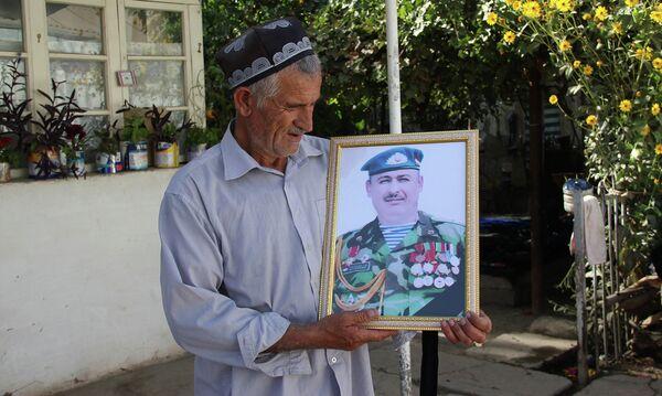 Отец погибшего Рустама Амакиева держит портрет сына - Sputnik Таджикистан