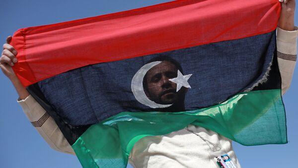 Житель Бенгази с флагом Ливии. Архивное фото - Sputnik Таджикистан