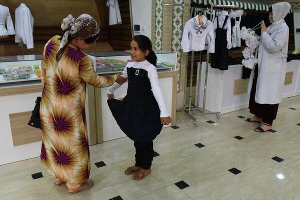 Девочка меряет новую форму во время школьной ярмарки в торговом центре Пойтахт-90. Архивное фото - Sputnik Таджикистан