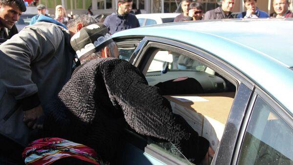 Близкие Зарины Юнусовой грузят гроб с телом Умарали Назарова в автомобиль - Sputnik Таджикистан