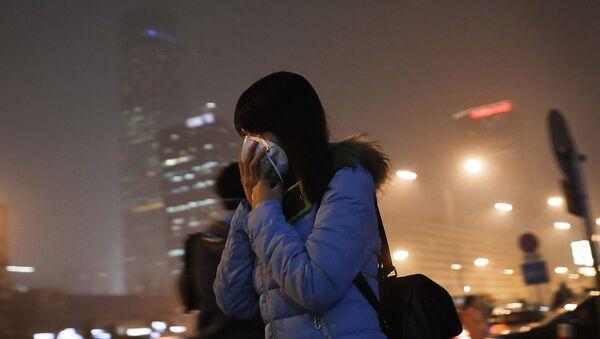 Женщина закрывает лицо маской во время выхода из метро в Пекине - Sputnik Таджикистан