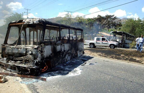 Сожженный демонстрантами автобус на улице городка Валенсия. Архивное фото - Sputnik Таджикистан