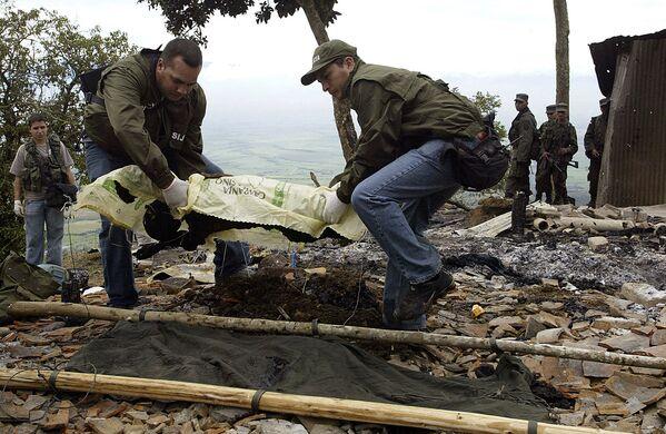 Колумбийские полицейские несут тело убитого товарища в районе города Пальмира (Колумбия). Архивное фото - Sputnik Таджикистан