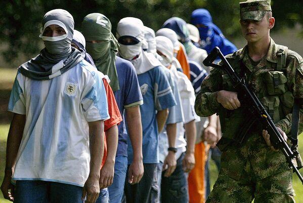 Колумбийский солдат ведет членов банды Лос Мачос, задержанных  в городе Кали (Колумбия). Архивное фото - Sputnik Таджикистан