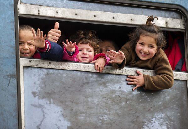 Мигранты выглядывают из окна поезда, следующему в Сербию через границы Греции и Македонии - Sputnik Таджикистан