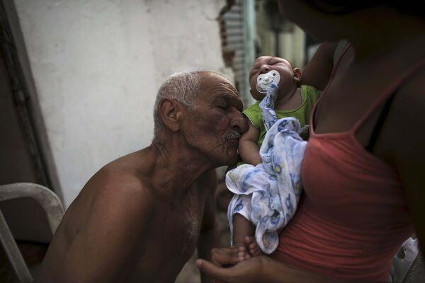 Мужчина целует своего двухмесячного внука, родившегося с микроцефалией в городе Ресиф (Бразилия) - Sputnik Таджикистан