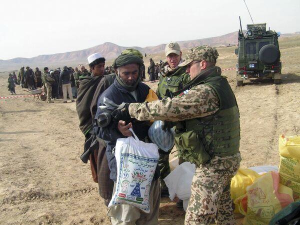 Военнослужащий финского подразделения в составе НАТО оказывает помощь местным жителям в провинции Балх (Афганистан). Архивное фото - Sputnik Таджикистан