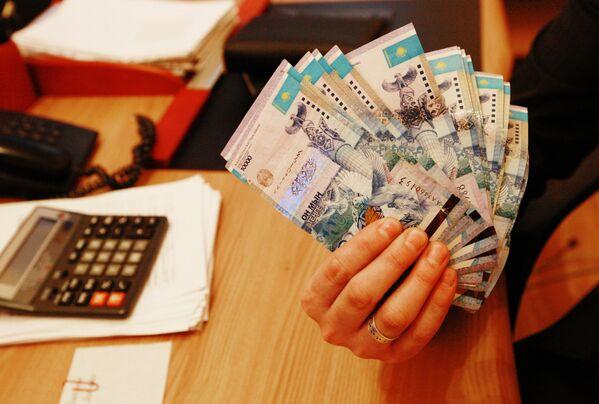 Тенге - национальная валюта Казахстана в одном из обменных пунктов в Алма-Ате. - Sputnik Таджикистан