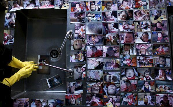 Волонтер очищает семейные фотографии, которые были испорчены впоследствии сильного землетрясения и цунами в марте 2011 года - Sputnik Таджикистан