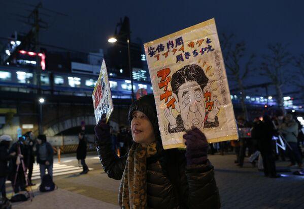Протестующая держит портрет японского премьер-министра Синдзо Абэ во время акции против ядерной энергетики в Токио. - Sputnik Таджикистан