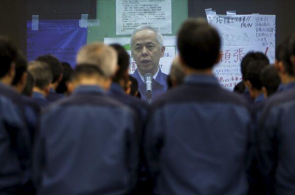 Рабочие Токийской энергетической компании (TEPCO) слушают речь президента компании Хиросэ Наоми на большом экране после минуты тишины в память о катастрофе 11 марта 2016 года. - Sputnik Таджикистан