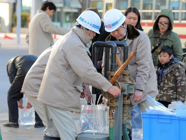 Служащие в городе Корияма раздают чистую воду жителям на следующий день после разрушительного землетрясения и аварии на АЭС Фукусима - Sputnik Таджикистан