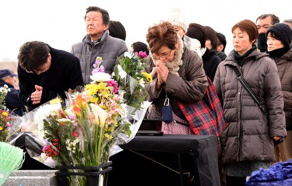 Люди молятся в память о жертвах разрушительного землетрясения и цунами 2011 года во время акции памяти в японском городе Сендай 11 марта 2016 года - Sputnik Таджикистан