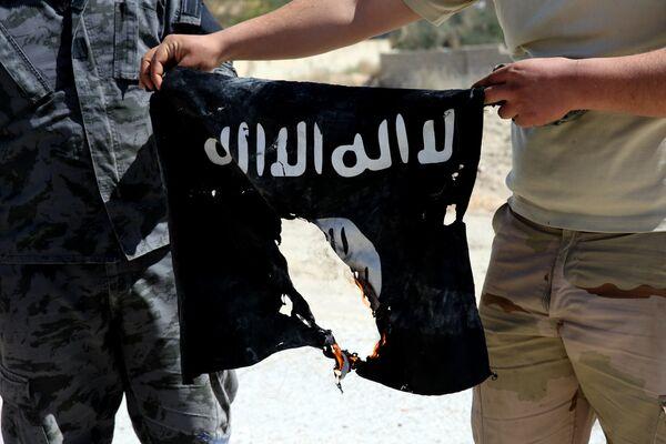 Сирийский военный сжигает флаг ИГ. Архивное фото - Sputnik Таджикистан
