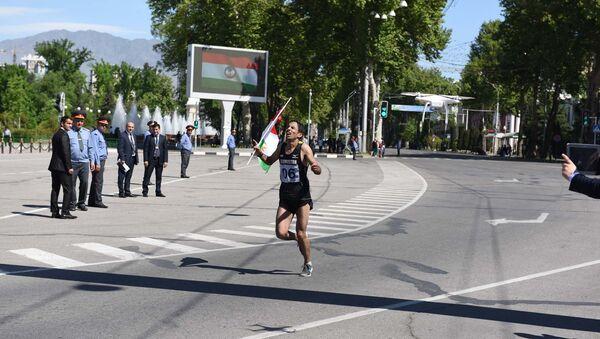 Мужчина с таджикским флагом на финишной прямой полумарафона в честь празднования Дня города в Душанбе - Sputnik Таджикистан