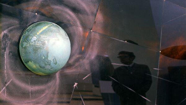 Схема магнитных полей и радиационных поясов вокруг Земли на выставочном стенде. Архивное фото - Sputnik Таджикистан