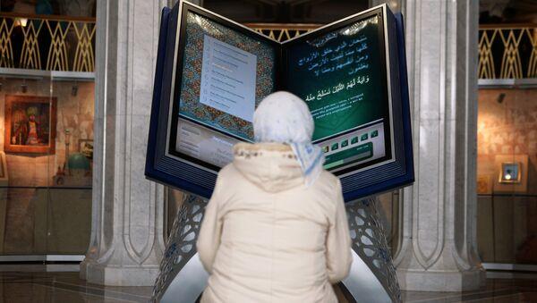Посетительница у электронного Корана на открытии выставки Серебряный Коран в музее исламской культуры в казанской мечете Кул-Шариф. Архивное фото - Sputnik Таджикистан