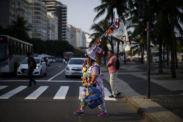 Женщина в одежде с символикой Олимпиады в районе пляжа Копакабана в Рио-Де-Жанейро - Sputnik Таджикистан
