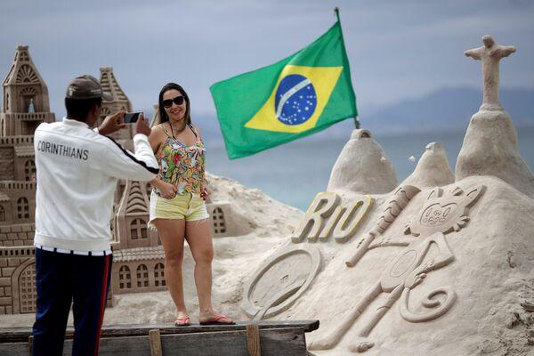 Женщина позирует на фоне песчаных скульптур на пляже Копакабана в Рио-Де-Жанейро - Sputnik Таджикистан
