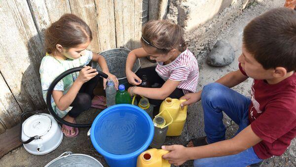 Дети набирают воду в пустую тару, архивное фото - Sputnik Таджикистан