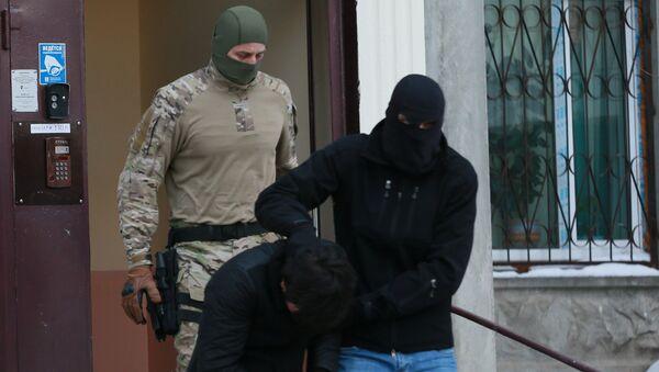 Силовики выводят из подъезда дома  одного из участников диверсионно-террористической группы, архивное фото - Sputnik Таджикистан