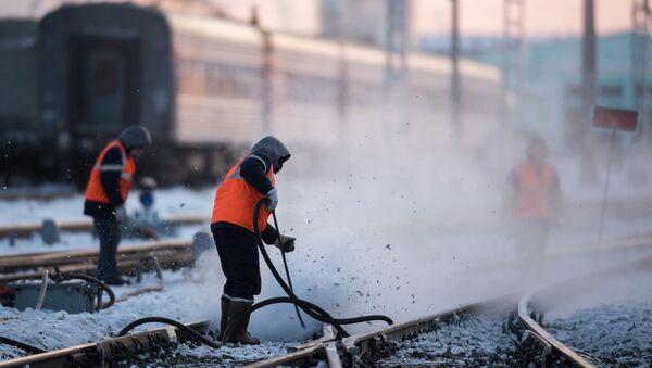 Рабочие очищают железнодорожный путь на станции, архивное фото - Sputnik Таджикистан
