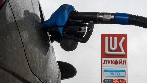 аправочный пистолет в бензобаке автомобиля на автозаправочной станции Лукойл, архивное фото - Sputnik Таджикистан