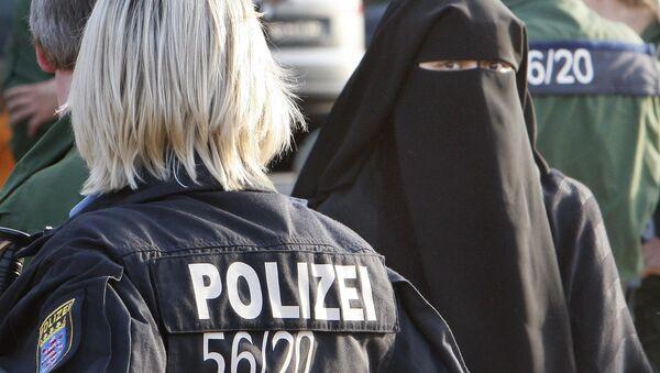 Сотрудница полиции Германии стоит напротив девушки в мусульманской одежде - Sputnik Таджикистан