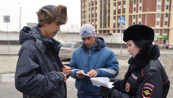 Лейтенант полиции проверяет документы у мигрантов - Sputnik Таджикистан