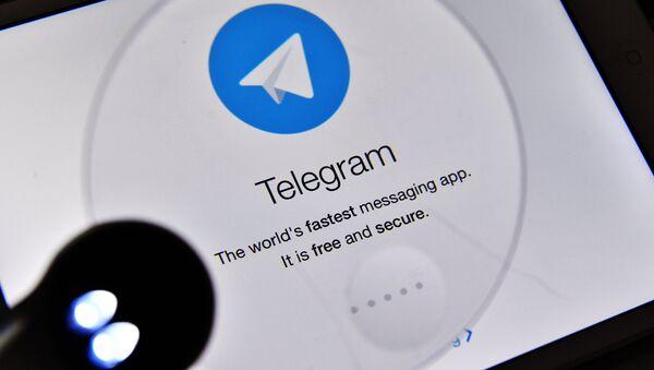 Логотип мессенджера Telegram на экране планшета, архивное фото - Sputnik Тоҷикистон
