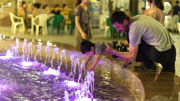 Мужчина играет у фонтана с ребенком, архивное фото - Sputnik Тоҷикистон