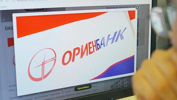 Логотип Ориёнбанка на экране монитора, архивное фото - Sputnik Таджикистан