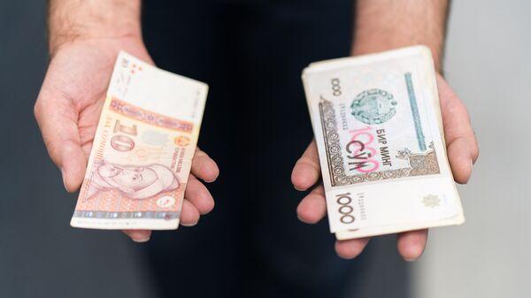 Узбекские и Таджикские деньги в руках, архивное фото - Sputnik Тоҷикистон