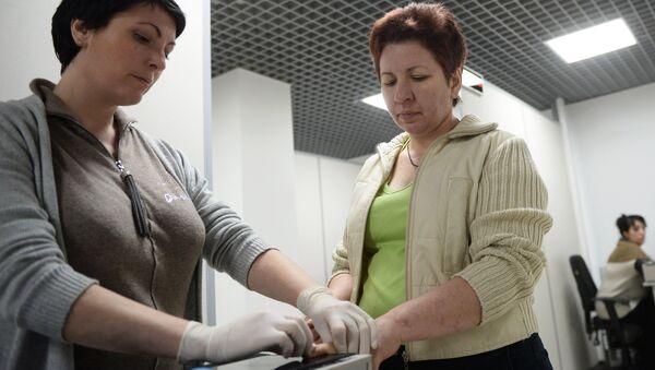 Иностранная гражданка (справа) проходит дактилоскопическую регистрацию, архивное фото - Sputnik Таджикистан