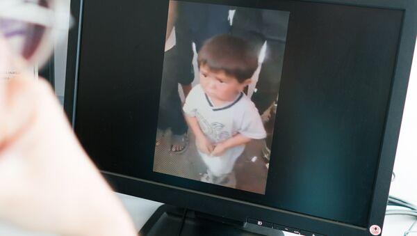 Просмотр на экране как маленький мальчик поет на одном из рынков в Таджикистане - Sputnik Тоҷикистон