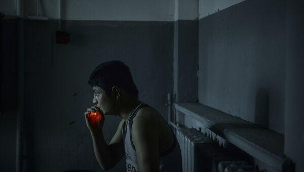 Иностранный рабочий курит во время задержания, архивное фото - Sputnik Таджикистан