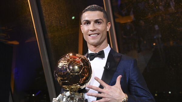 Криштиану Рональдо держит Золотой мяч, который он получил в четверг 7 декабря 2017 года в Париже - Sputnik Тоҷикистон