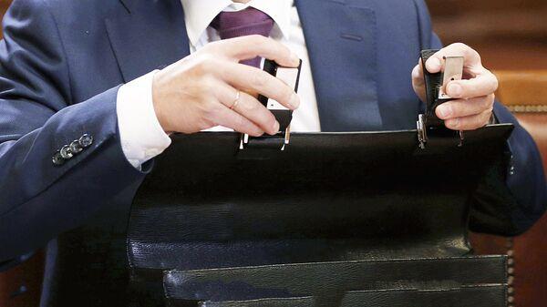 Мужчина закрывает портфель, архивное фото - Sputnik Тоҷикистон