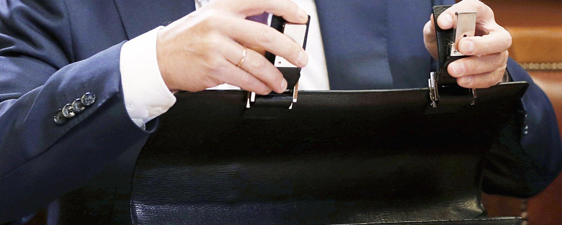 Мужчина закрывает портфель, архивное фото - Sputnik Тоҷикистон, 1920, 19.07.2021